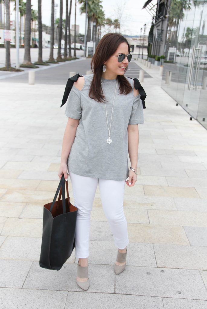 Lady in Violet styles a spring casual outfit including a gray cold shoulder tee, white skinny jeans, and gray suede heels.