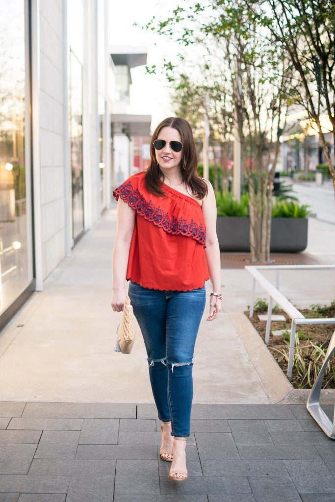Lady in Violet wears a spring casual weekend outfit with heels, jeans, and a one shoulder top.