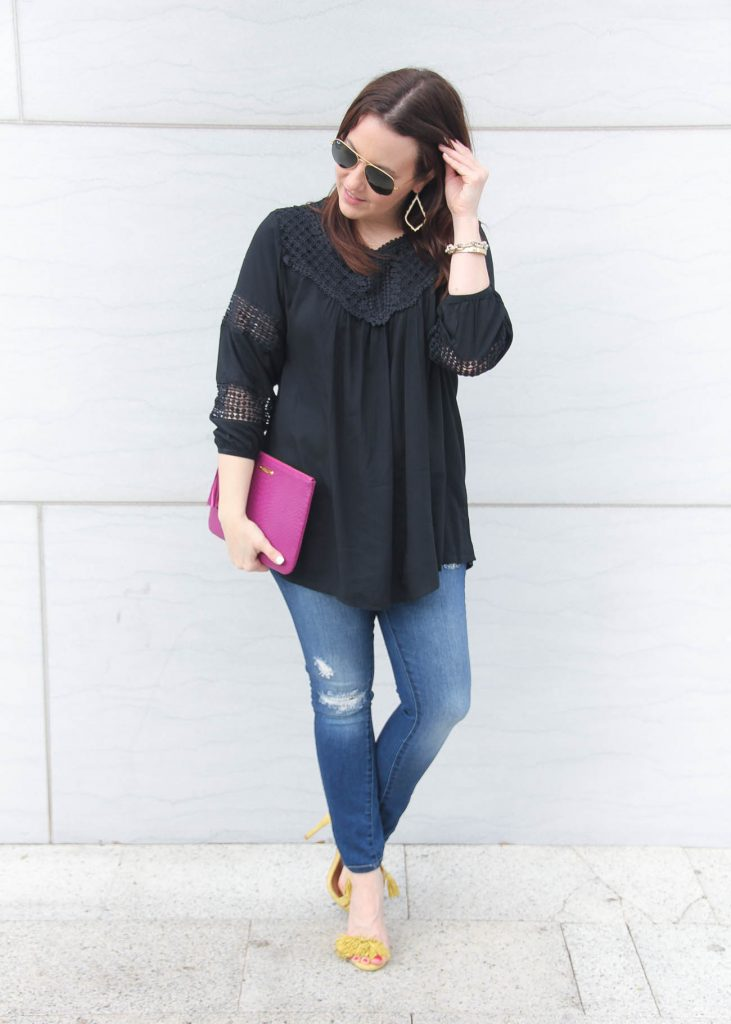 Houston fashion blogger wears a spring outfit idea featuring distressed jeans, black flowy top and yellow sandals.