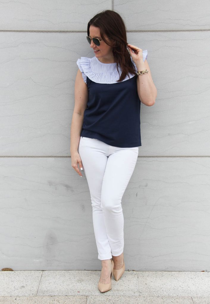 Spring outfit including white jeans, nude heels, and a navy sleeveless top.