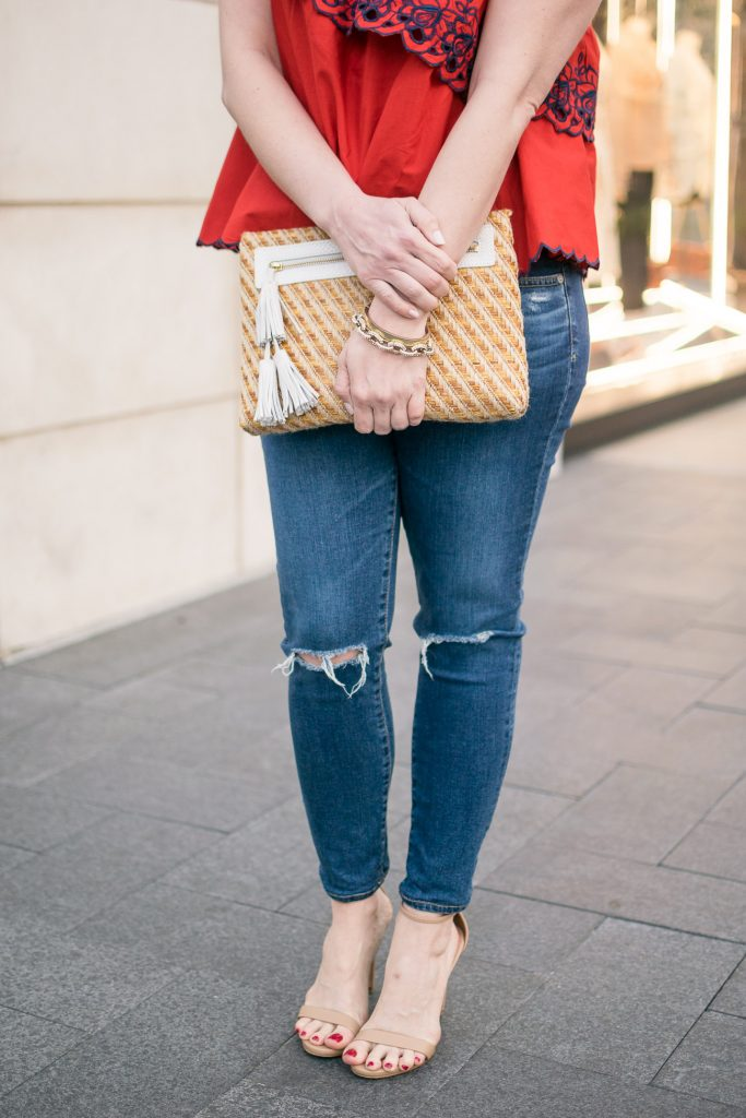 Lady in Violet, a Houston based fashion blogger, carries a cute spring clutch with white tassels and wears ag distressed jeans and steve madden stecy sandals.