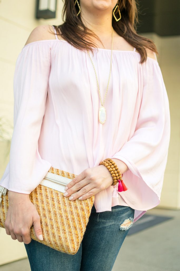 Houston style blogger styles the spring trend a pink cold shoulder top with pink tassel bracelets.