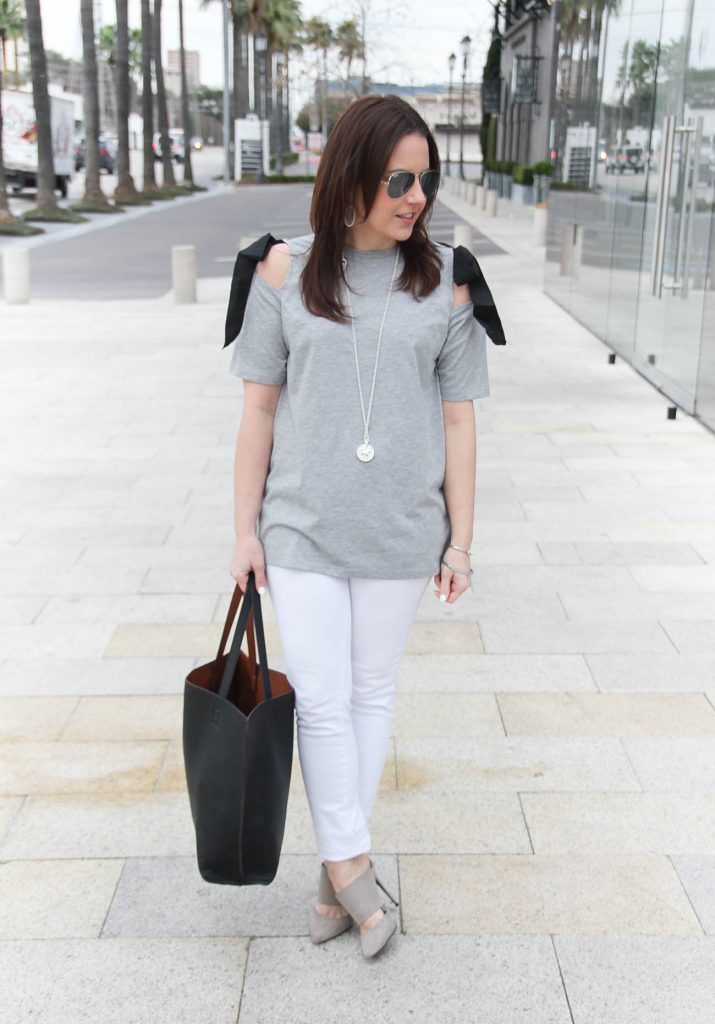 Karen Rock, a Houston fashion blogger wears a spring weekend outfit idea including gray bow shoulder tee, white jeans, and gray heels.