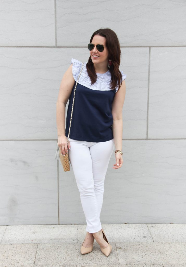 Lady in Violet styles a summer outfit including white jeans and a navy ruffle tee with heels.