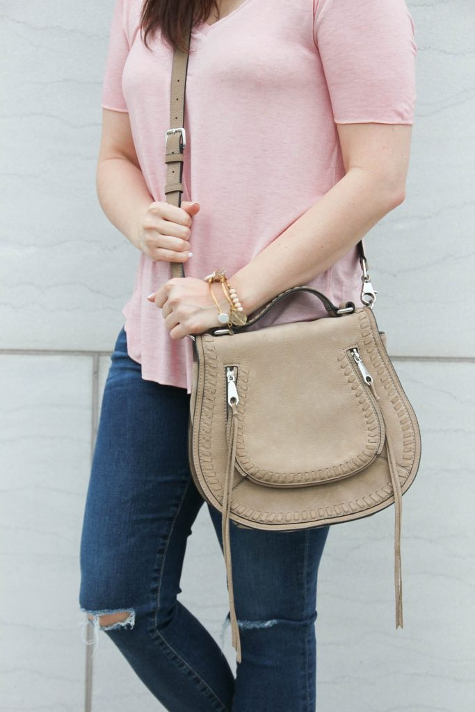 Houston fashion blogger styles casual summer outfit inspiration including a pink tshirt, jeans, and a chloe saddle bag dupe.