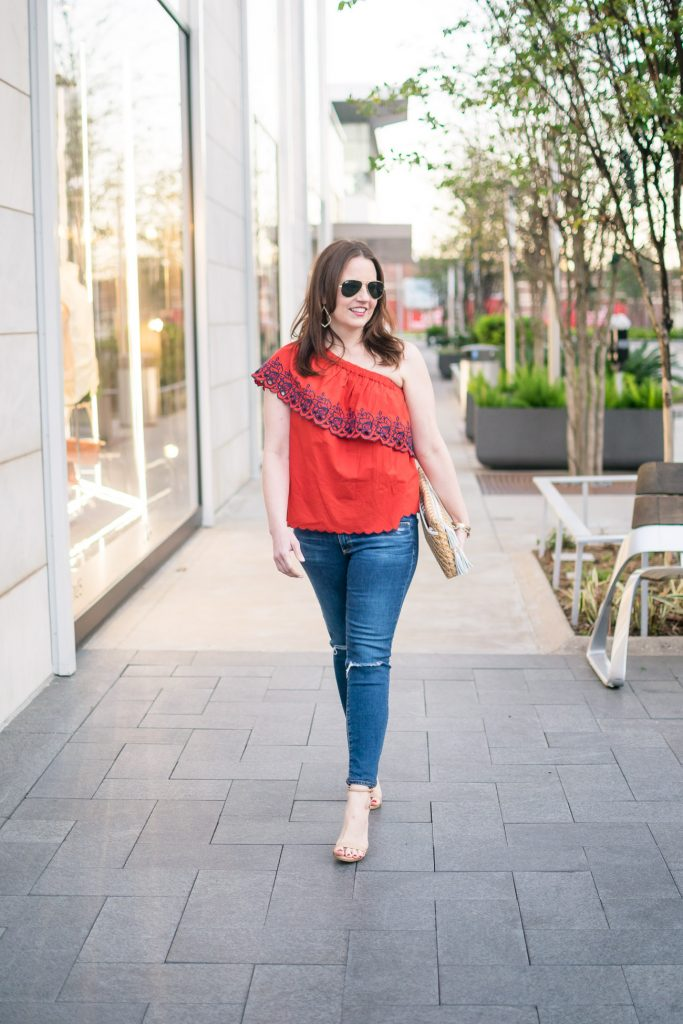Houston fashion blogger styles spring outfit ideas with a one shoulder top and distressed jeans.