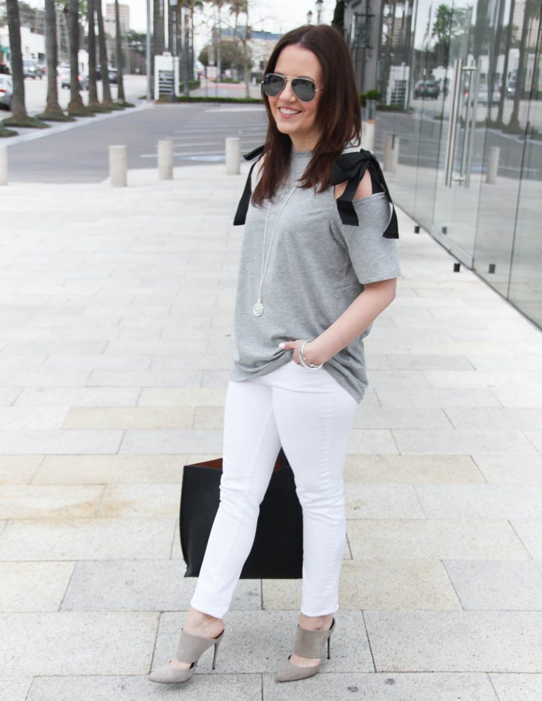 Houston fashion blogger, Lady in Violet, wears a spring outfit idea including a gray cold shoulder tee, white jeans, and gray heels.