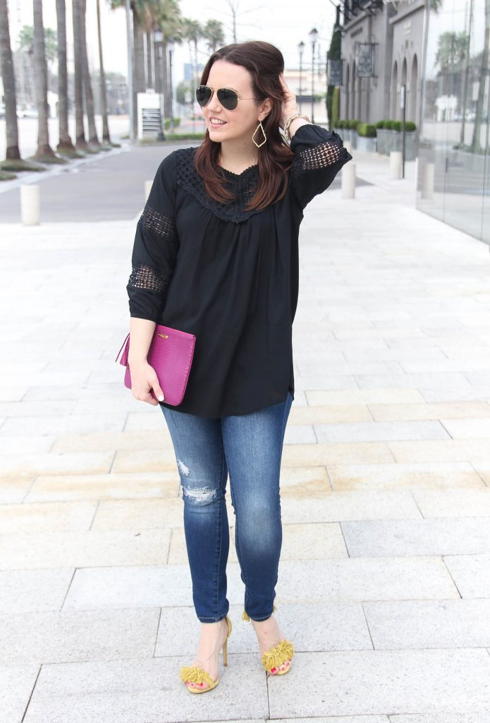 Houston Fashion Blogger wears spring outfit idea including black crochet blouse, distressed jeans, and yellow fringe sandals.