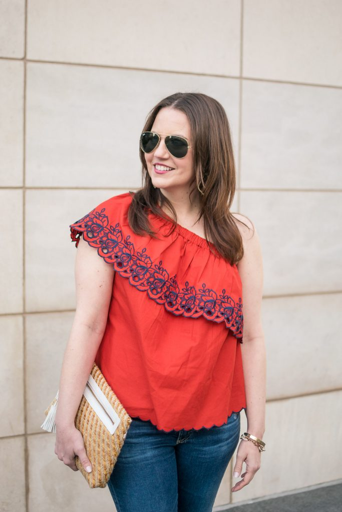 Houston fashion blogger styles a summer party outfit idea including a red one shoulder top with jeans and a cute clutch.