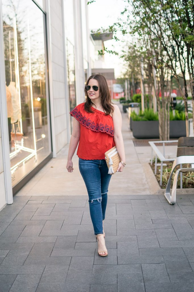 Fashion blogger shows houston street style in a spring outfit idea featuring a red one shoulder top with distressed jeans.