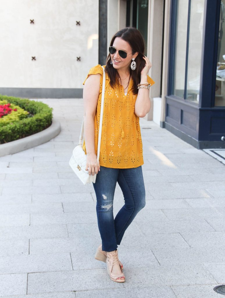 Houston fashion blogger Lady in Violet styles a causal weekend outfit including a yellow top with distressed jeans and nude wedges.