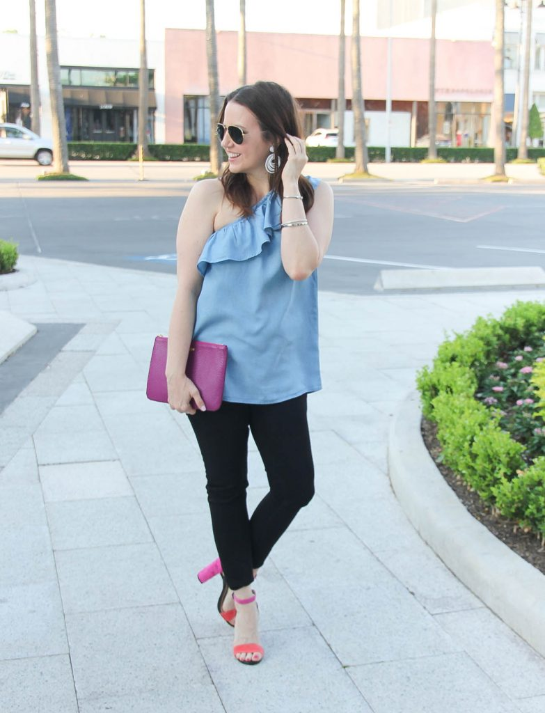 Houston fashion blogger styles spring outfit idea featuring chambray one shoulder top with black skinny jeans and block heel sandals.