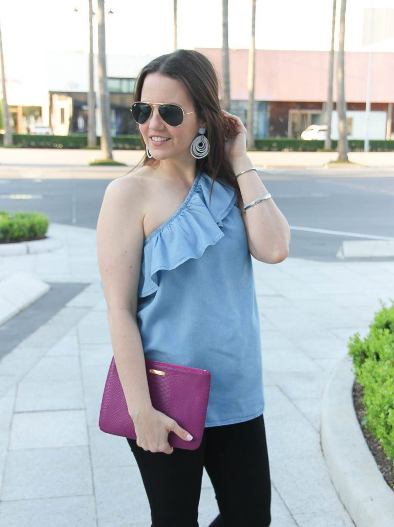 Karen Rock, a Houston fashion blogger wears chambray ruffle one shoulder top with white statement earrings.