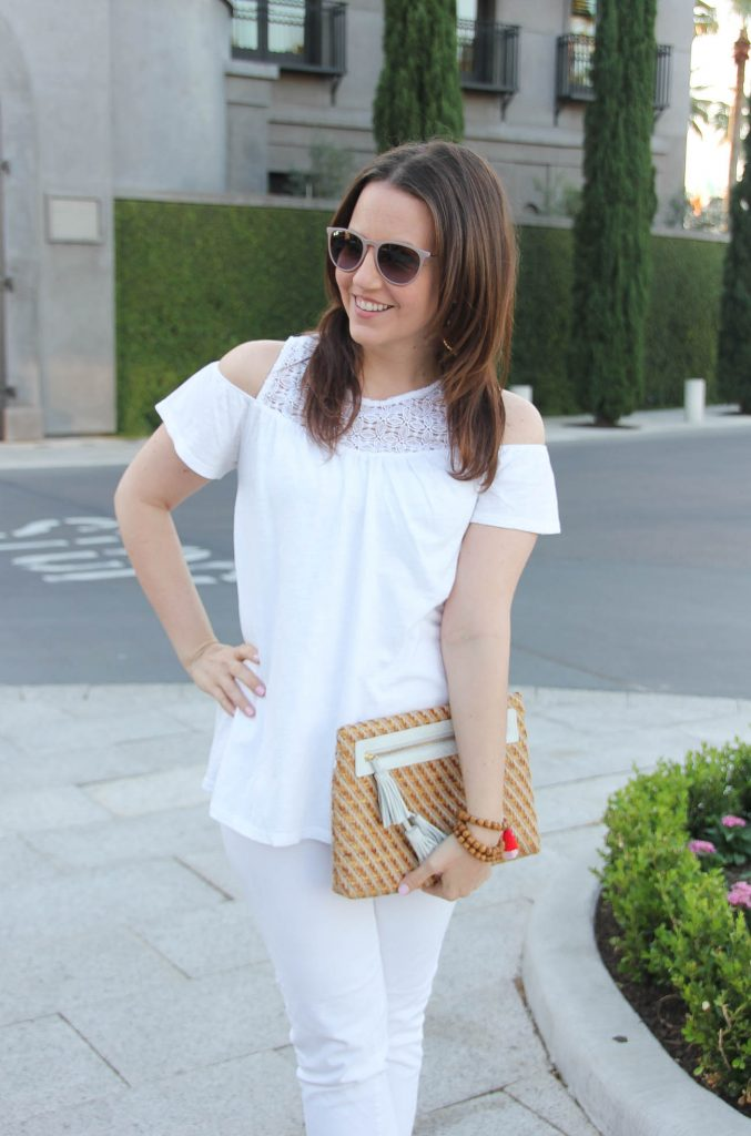Lady in Violet, a Houston based style blogger, wears a spring white on white outfit including a cold shoulder top, white jeans, and a cute straw clutch with white tassels.
