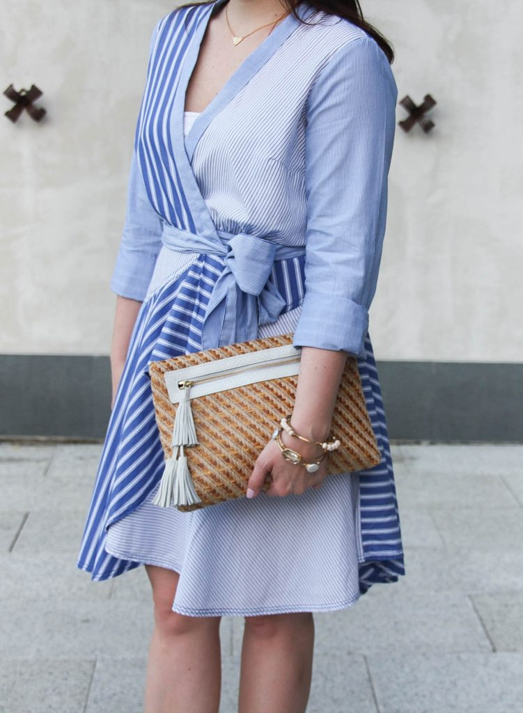 Houston blogger wears a striped blue Easter dress with a straw clutch with tassel.