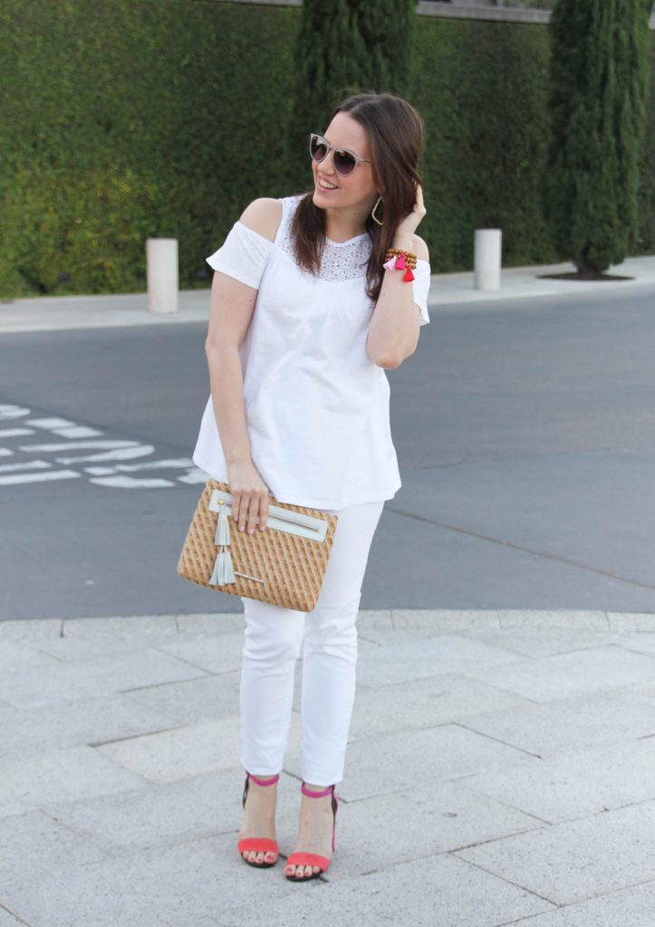 Karen Rock, a Houston fashion blogger, styles a spring outfit including a white cold shoulder top with white jeans and pink block heel sandals.