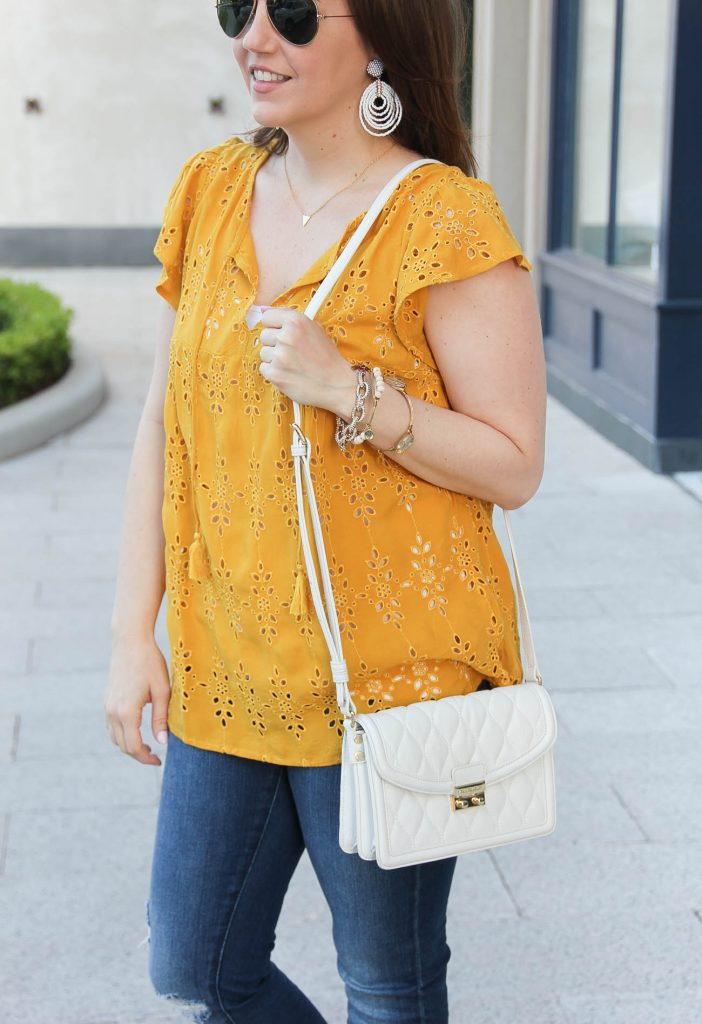 Houston fashion blogger Lady in Violet carries the Vera Bradley leather bag for a summer outfit idea with yellow top.