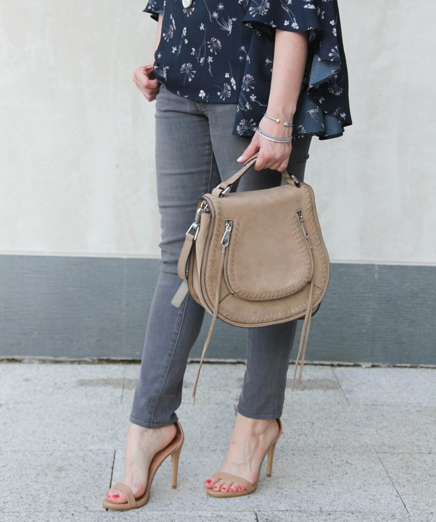 Houston fashion blogger Lady in Violet carries the Rebecca Minkoff vanity saddle bag and wears gray skinny jeans and Steve madden Stecy sandals.