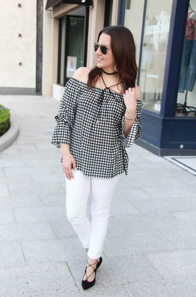 Houston fashion blogger wears spring outfit ideas including gingham off the shoulder top with bell sleeves and white denim with black heels and a choker necklace.