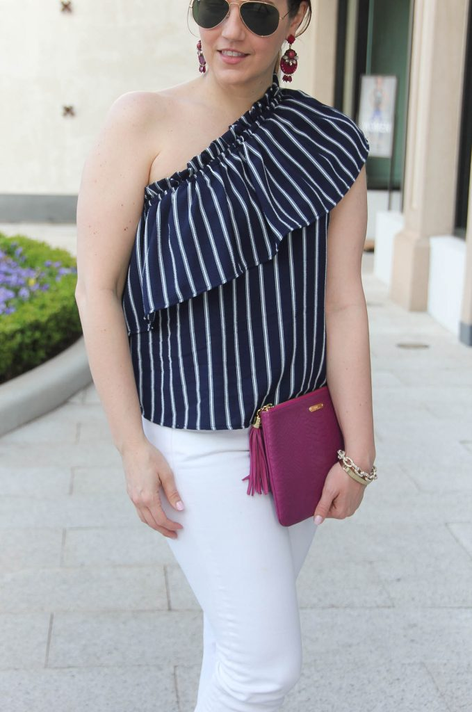 Personal style blogger Lady in Violet styles spring trends including a ruffle one shoulder top with white skinny jeans.