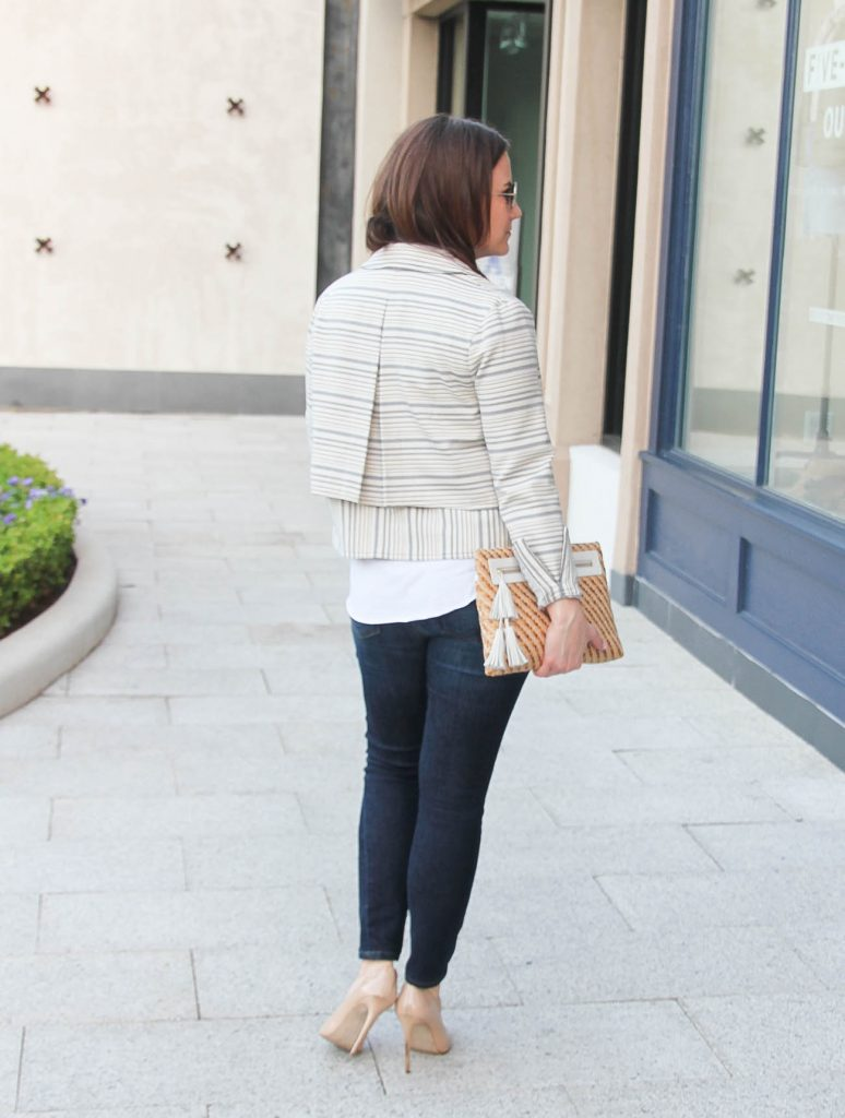 Spring Outfit idea including striped spring jacket, dark skinny jeans, and a cute tassel clutch bag.