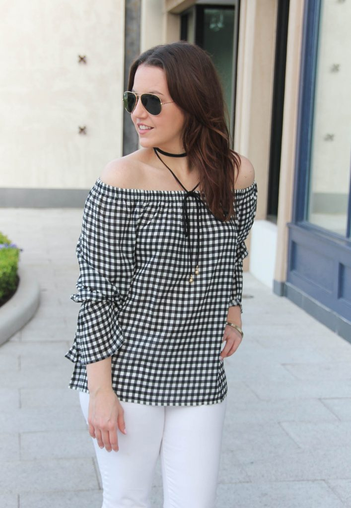 Lady in Violet, a Houston fashion blogger, wears a dressy casual outfit idea including a gingham off the shoulder top with a choker necklace and white jeans.
