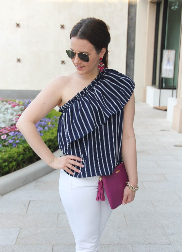 Lady in Violet, a Houston fashion blogger, wears a dressy casual weekend outfit idea including a one shoulder top with jeans.