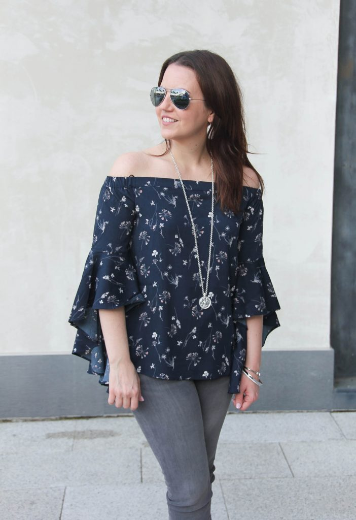 Lady in Violet, a Houston based fashion blogger wears a Nordstrom floral bell sleeve off the shoulder top with gray jeans.