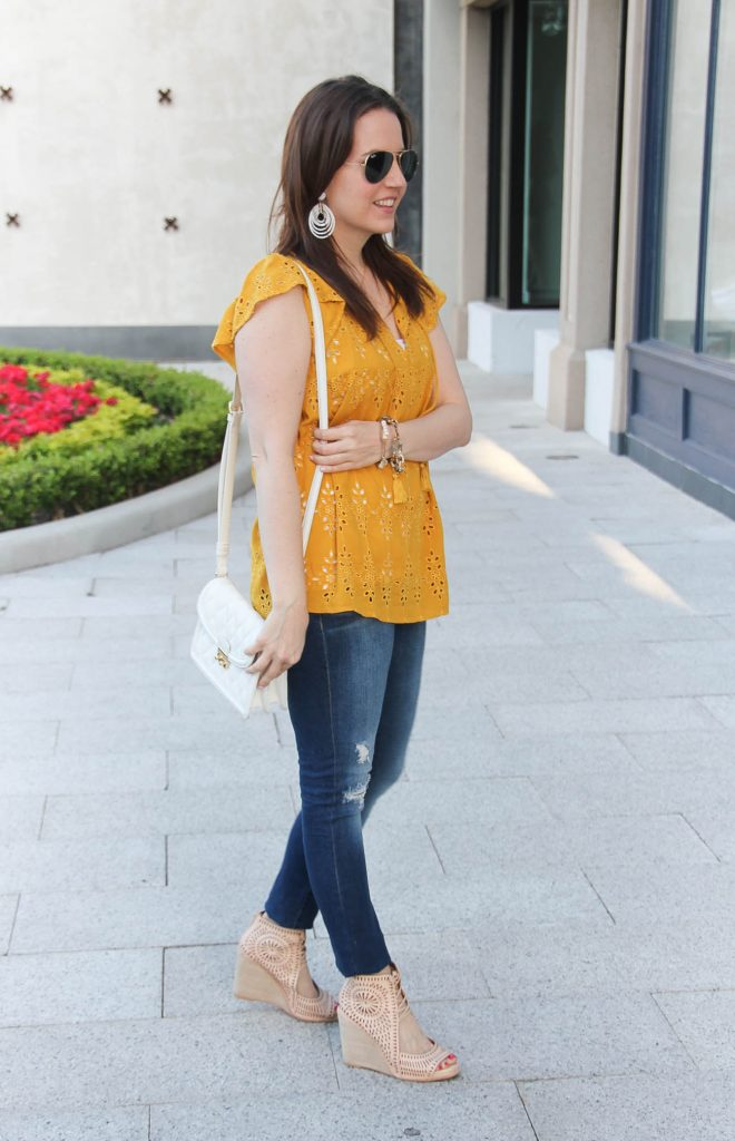 Houston blogger Lady in Violet styles a casual weekend outfit including a yellow top with distressed jeans and wedges.
