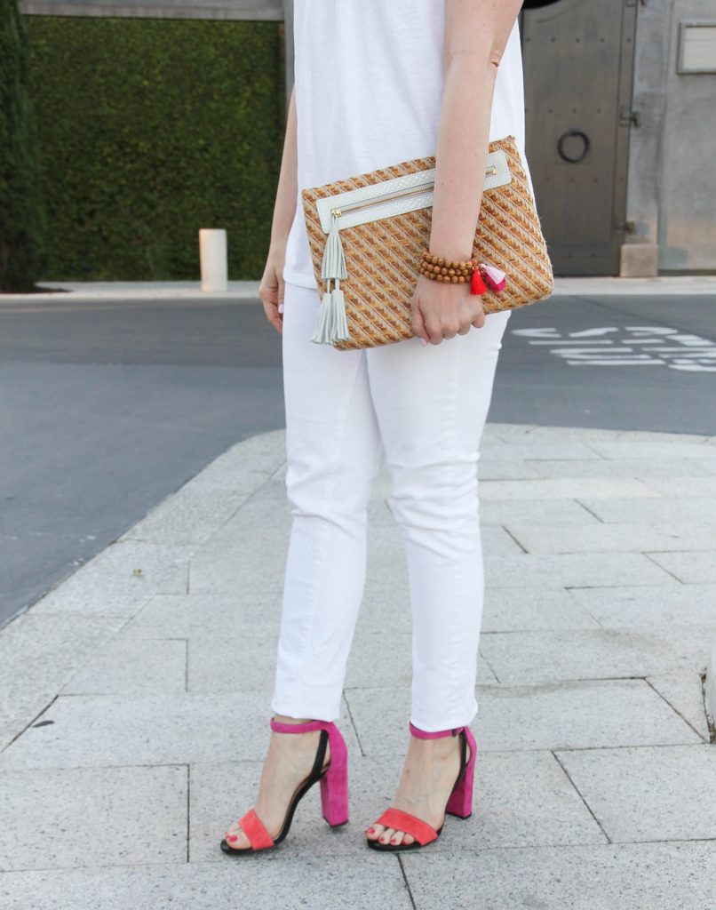 Personal Style blogger from Houston wears pink and coral block heel sandals with white skinny jeans and an Elaine Turner clutch.