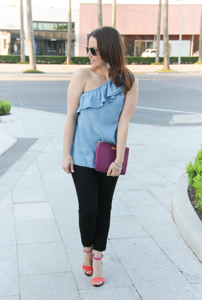 Houston blogger Lady in Violet styles spring outfit including chambray one shoulder top with black jeans and block heel sandals.