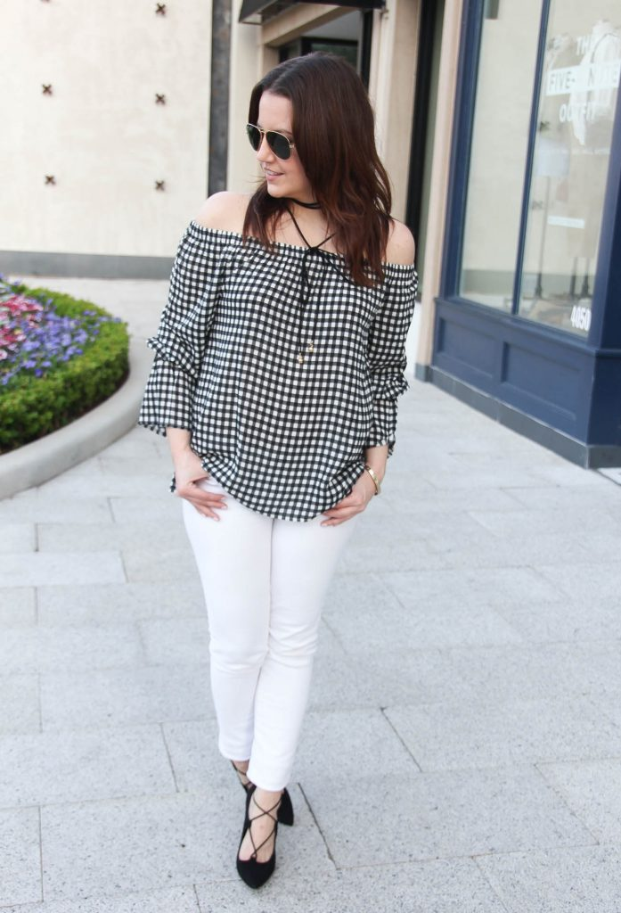 Houston fashion blogger styles a spring outfit idea including gingham bell sleeve top with white jeans and black lace up heels.