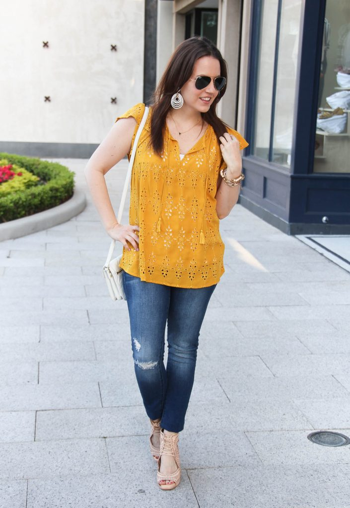Houston fashion blogger Lady in Violet wears casual weekend outfit including yellow top with distressed jeans and wedge sandals.