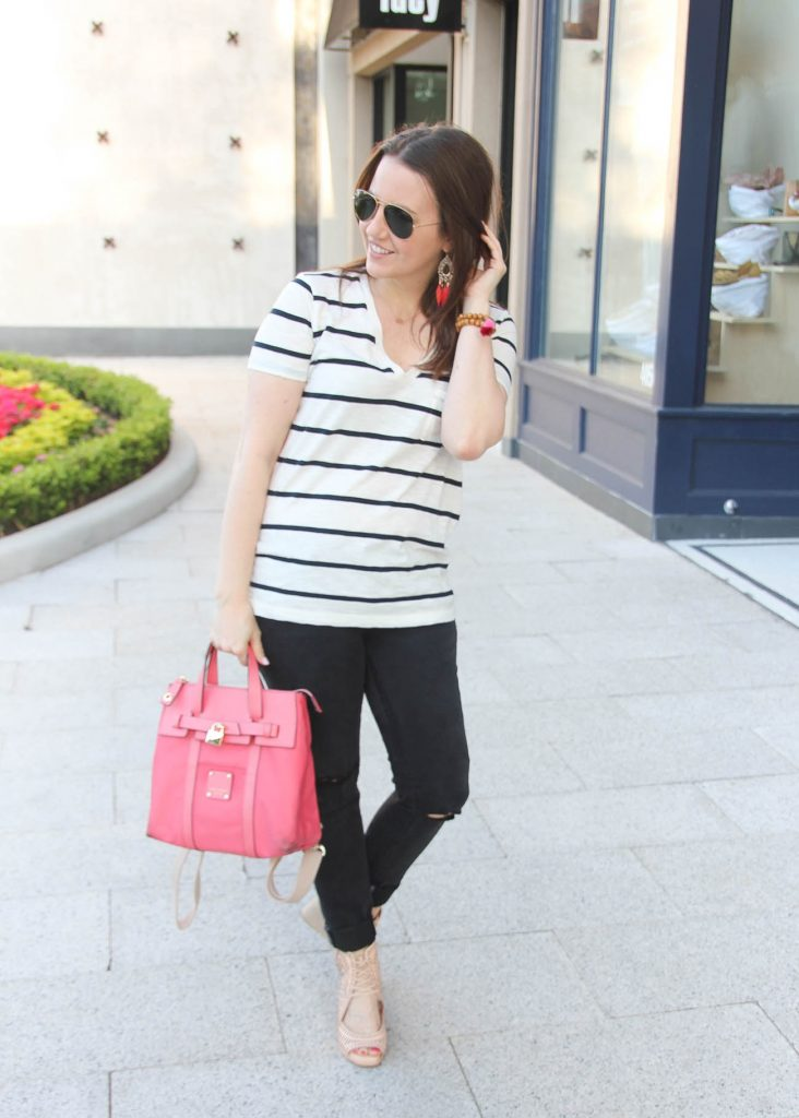 Houston style blogger wears casual spring outfit idea including striped tee, black skinny jeans, wedges, and pink backpack.