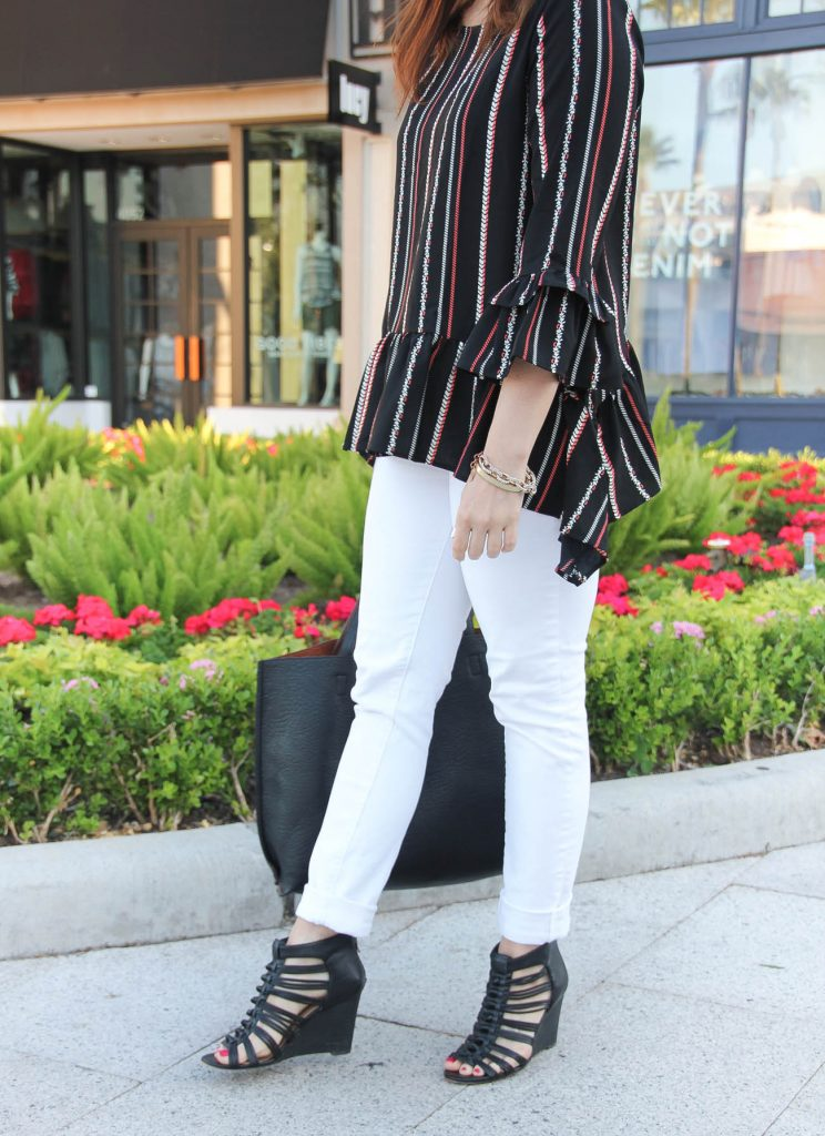Houston fashion blogger styles spring outfit inspiration including white jeans, black wedge sandals, and peplum blouse.