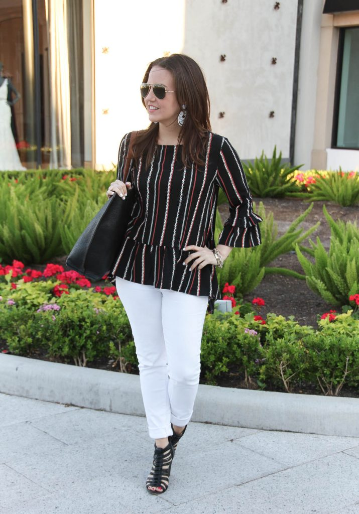 spring outfit including peplum top, white skinny jeans, and affordable black tote bag