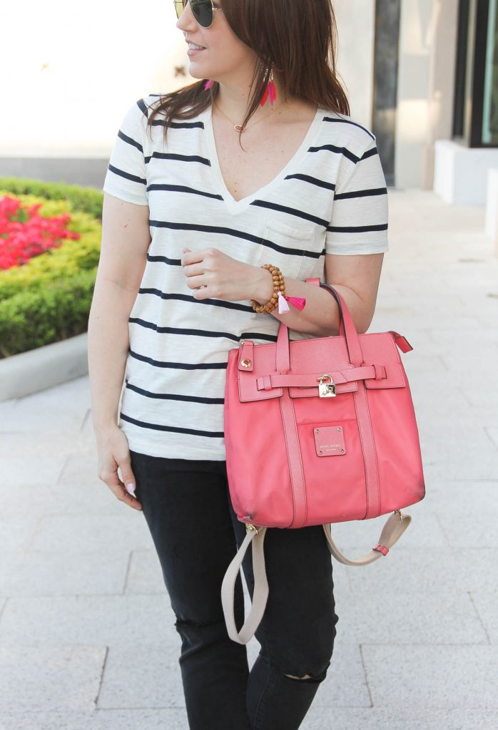 Houston blogger wears casual striped tee and distressed jeans with pink purse.