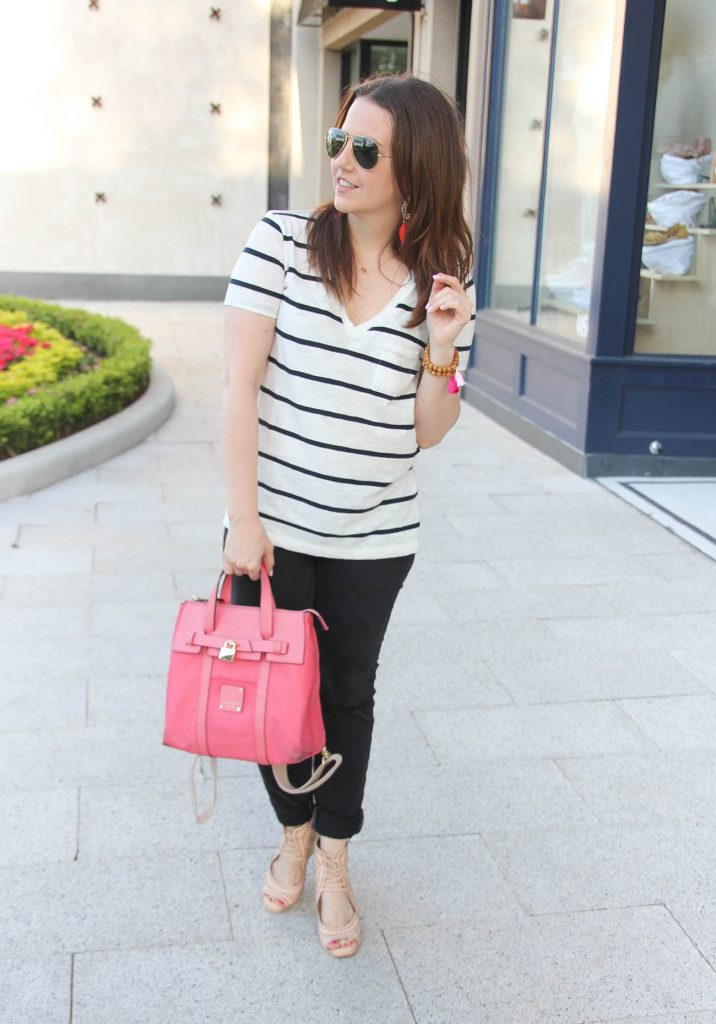 Houston fashion blogger styles casual outfit inspiration including striped tee with black jeans and nude wedges paired with pink bag.