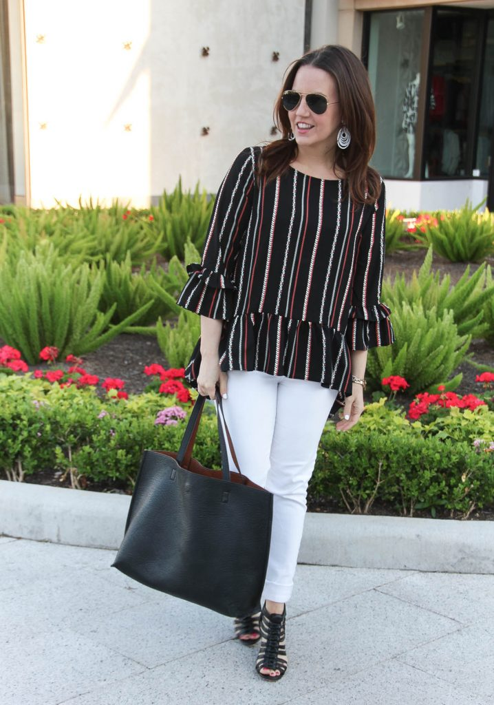 Houston style blogger wears spring outfit ideas including white jeans, peplum top and black tote bag.